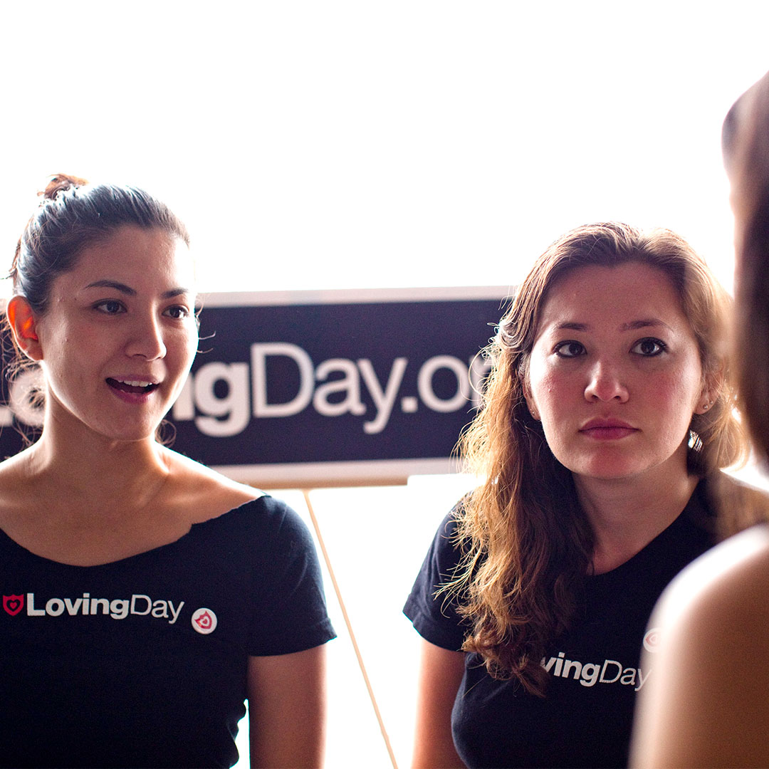 Two women volunteering and wearing Loving Day t-shirts who are standing behind a Loving Day sign and speaking to a guest at Loving Day NYC 2010.