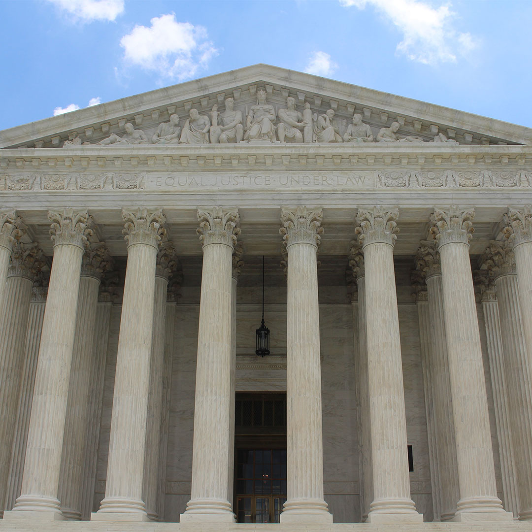 Front of the U.S. Supreme Court building, which is made of white stone, considered to be Neoclassical style, with large columns, and has the inscription Equal Justice Under Law.
