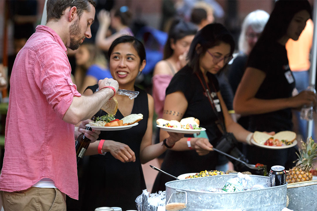 People in line at a buffet table serve themselves food at Loving Day NYC 2018.