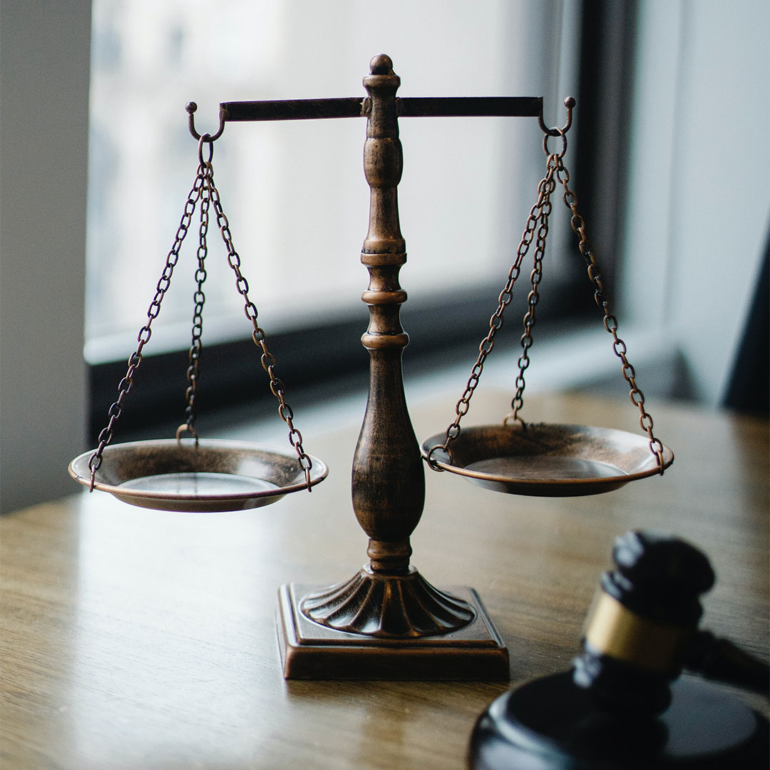 Scales of the type that are often used to symbolize justice and a gavel on a desk.