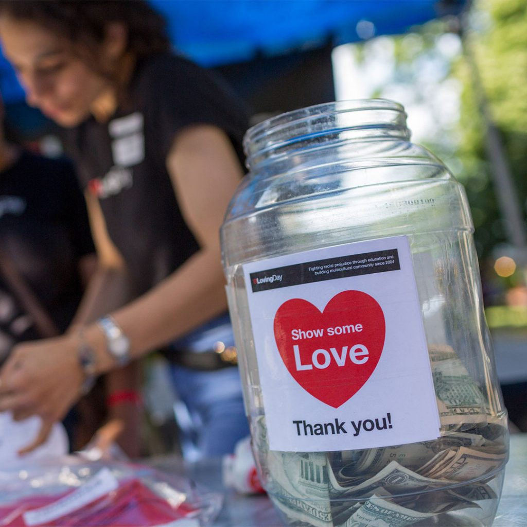 A transparent donation jar with some small bills inside and a label that says show some love in front of two volunteers at Loving Day NYC 2019.