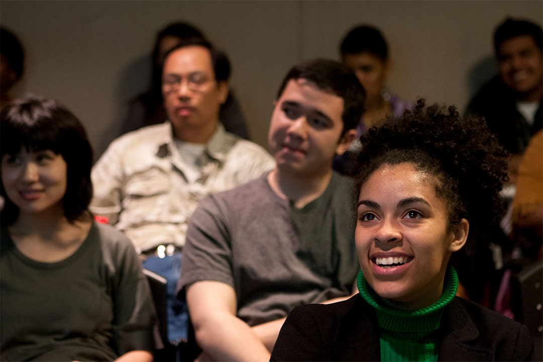 A young woman smiles as part of an audience indoors at a Loving Day educational event in 2012.