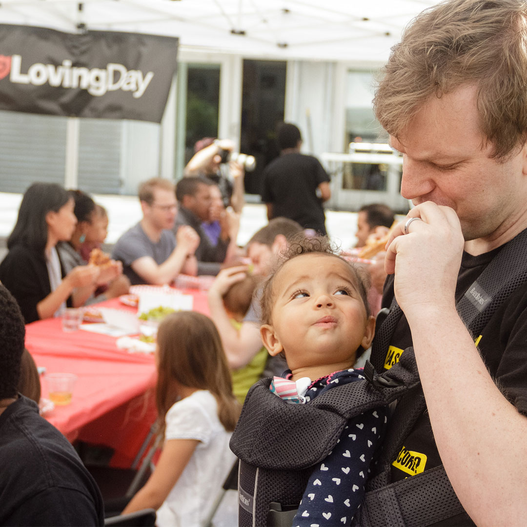 A baby in a baby carrier looks up at her father with a playful look at Loving Day NYC 2017.