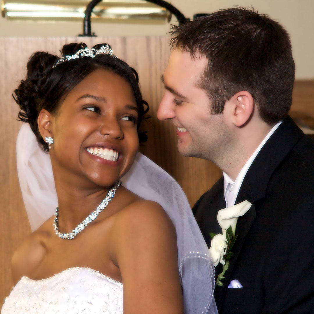 A wedding photo of a woman smiling and looking over her shoulder at her husband who is also smiling.