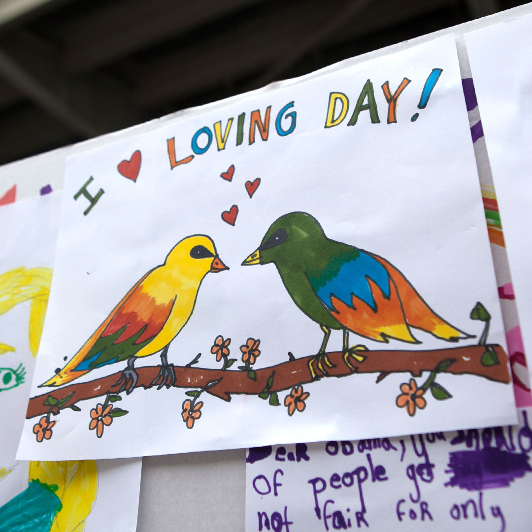 A marker drawing of two colorful birds facing each other with hearts and a title that says I heart Loving Day!