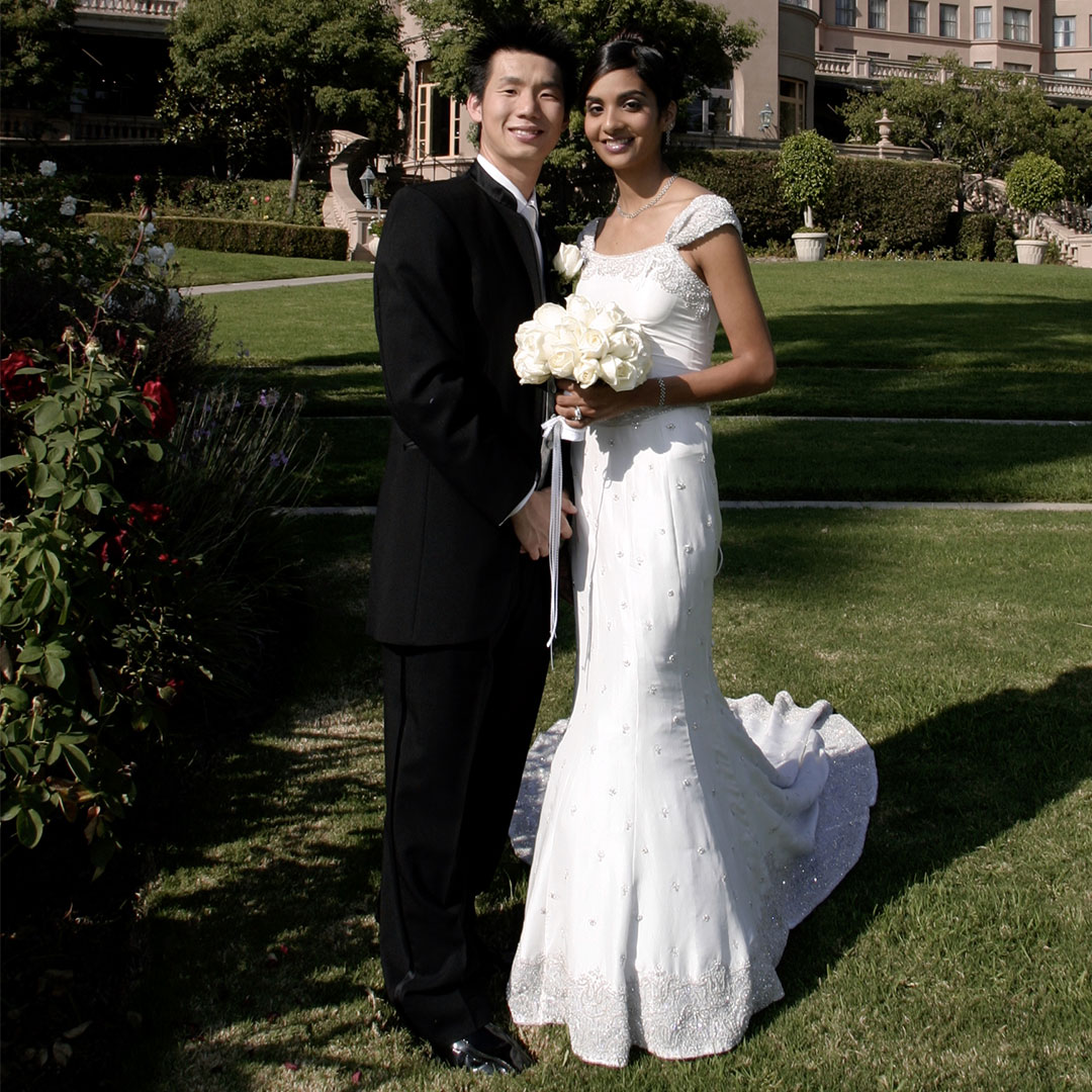 A wedding photo of a woman and a man smiling and standing outdoors on a grass outside of a large building.
