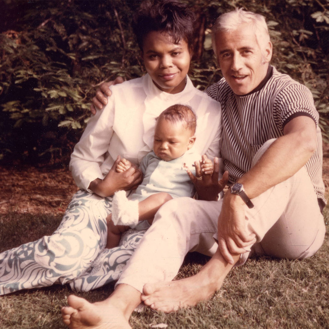 A faded family photo of a woman and a man smiling with a baby sitting outdoors on the grass.