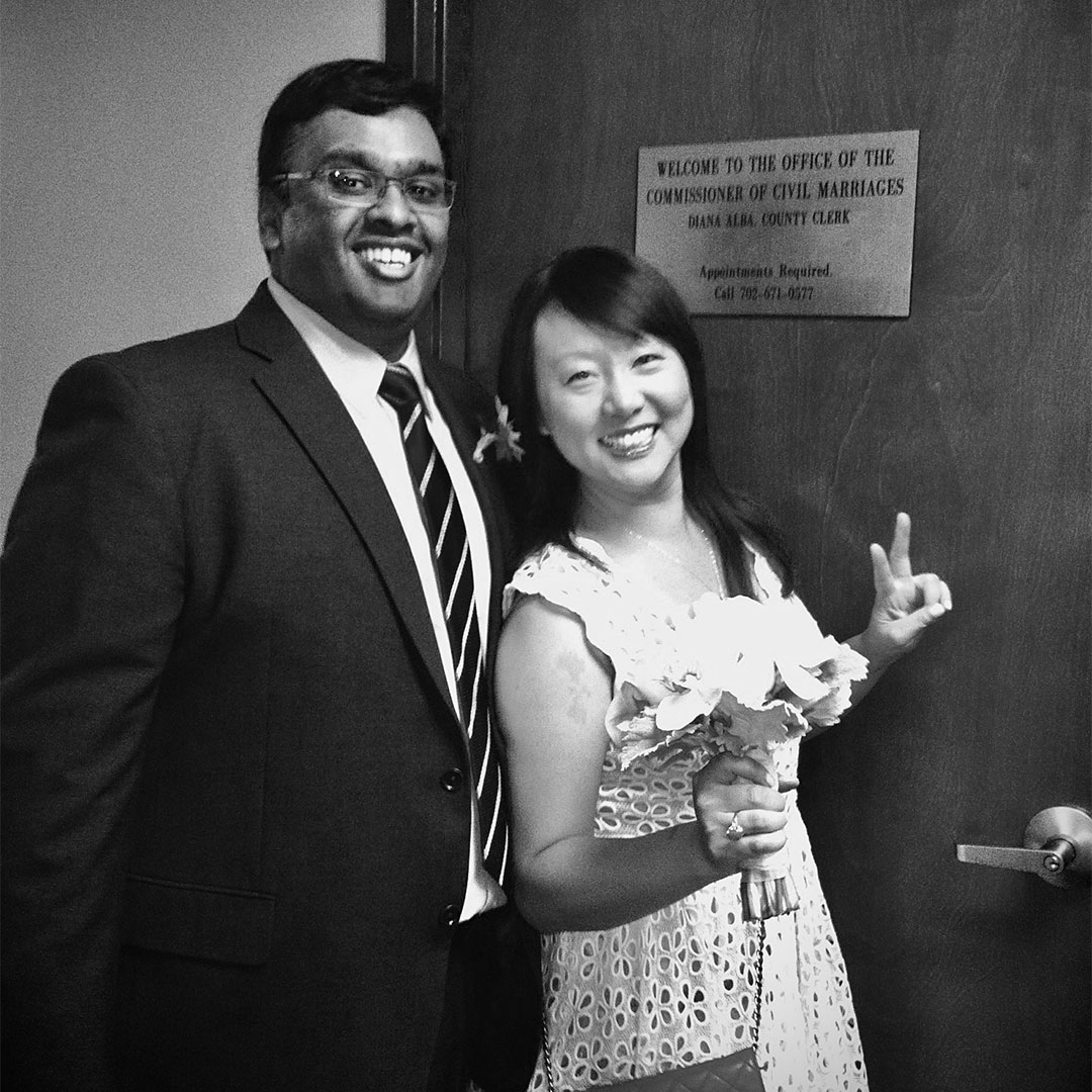 A wedding photo of a man and a woman holding a bouquet smiling indoors in front of a door with a sign that says Welcome to the office of the commissioner for civil marriages.