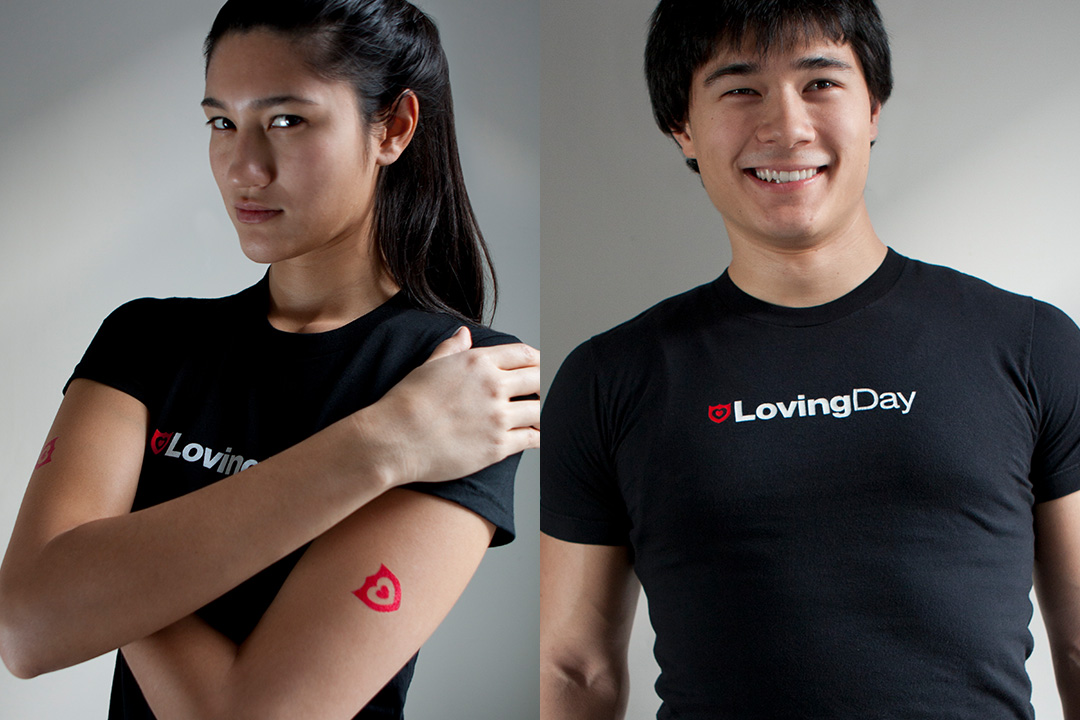 A woman and a man each wearing a black t-shirt with the Loving Day logo on it, and the woman also has a red Loving Day symbol temporary tattoo on her arm.