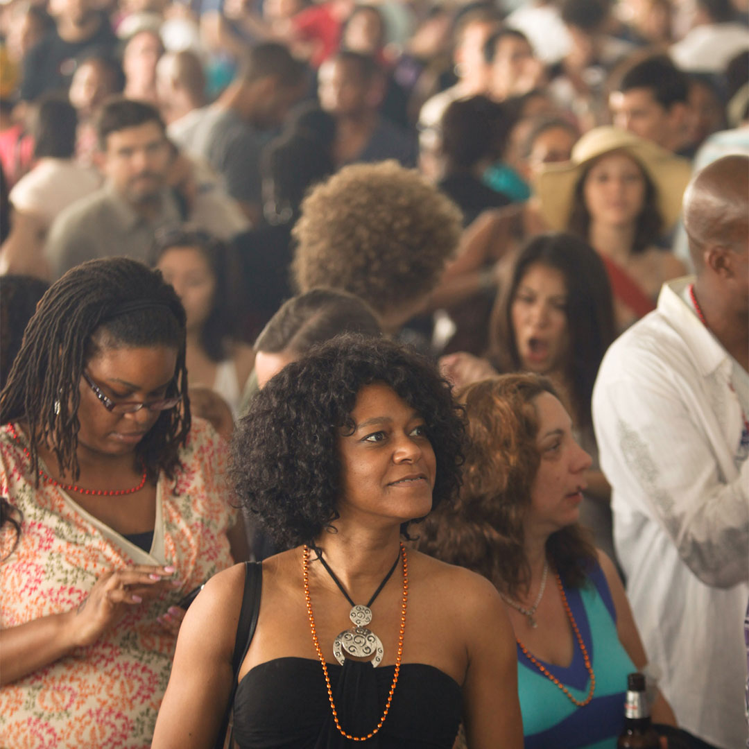 A woman smiles in a large group of attendees under a festival tent at Loving Day NYC 2011.