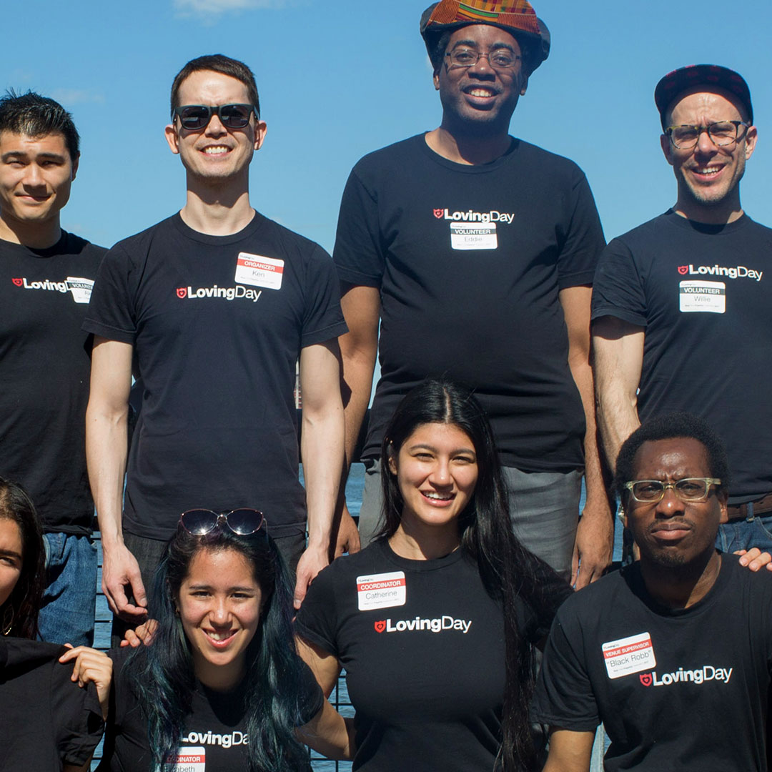 A group photo of seven volunteers including two women and five men who are wearing black t-shirts with the Loving Day logo and who vary in height and skin tone at Loving Day NYC 2017.