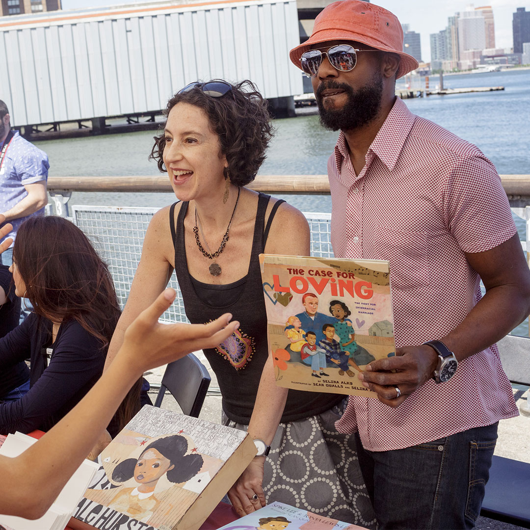 A woman and a man holding a children's book outdoors behind a table at Loving Day NYC 2016.