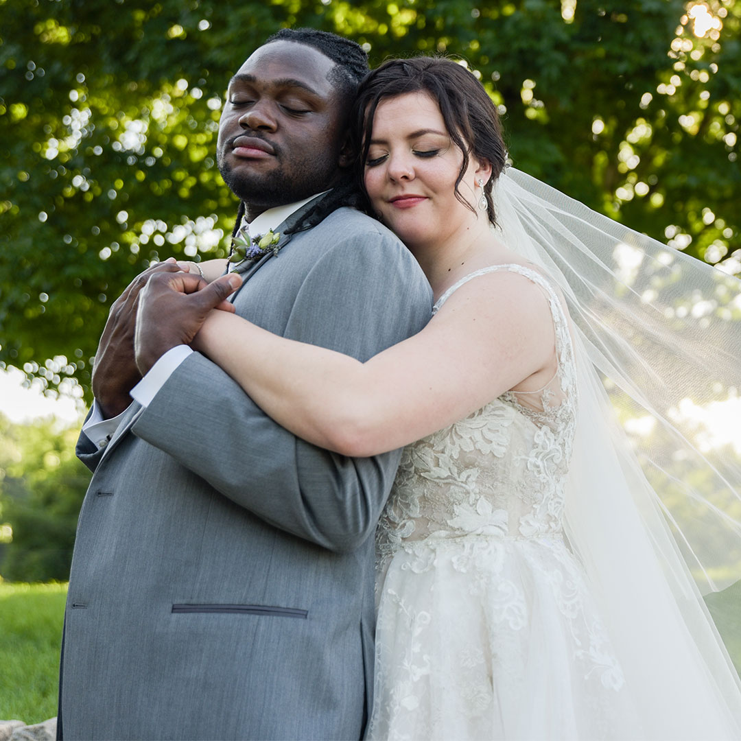 A wedding photo of a woman hugging a man from behind with their eyes closed, standing outdoors.