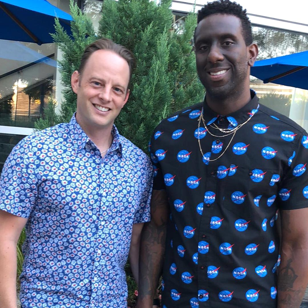 Two men holding hands, standing outside, wearing similar shirts, with a tree and some parasols behind them.