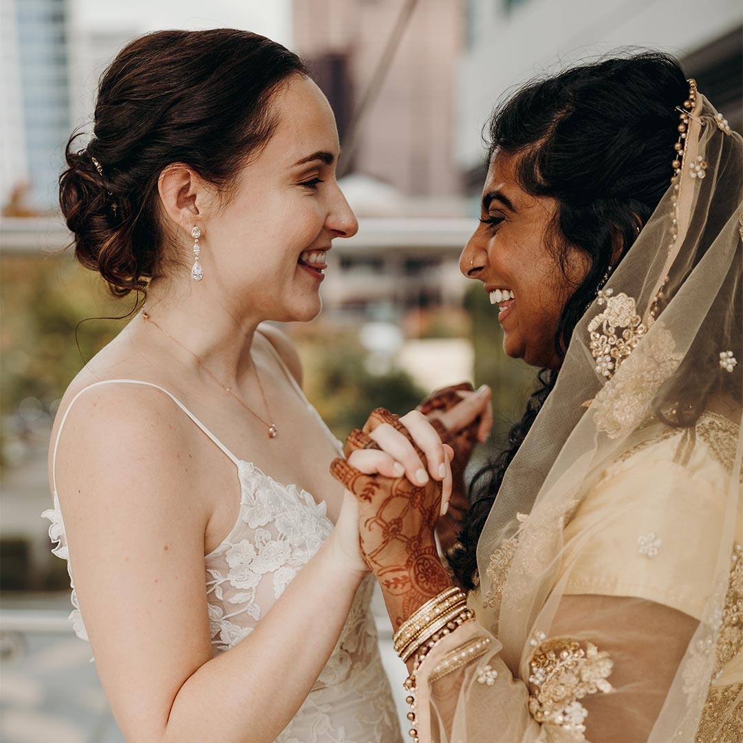 A wedding photo of two women outdoors, facing each other, smiling, and holding hands.